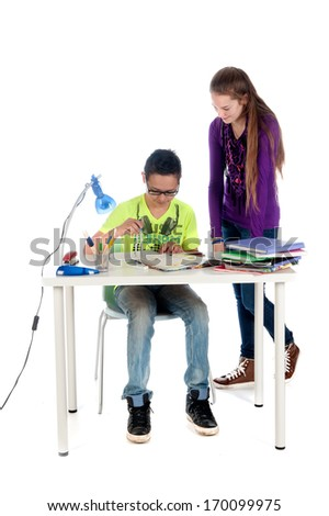 A teenage girl is helping a teenage boy with his math homework. - stock photo