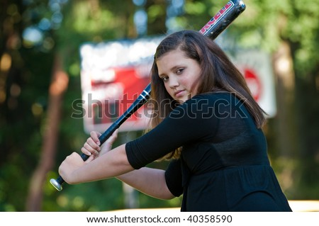 A teenage girl is ready to hit a softball