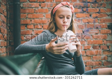 A teenage girl looks at her smartphone while drinking milkshake with brick wall in the background. Toned image