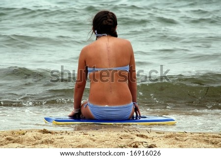 A teenage girl recently recovered from back surgery, sitting on the beach in summer. - stock photo