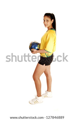 A teenage girl standing in profile, in a soccer uniform and holding the ball, with her long black hair in a ponytail for white background.