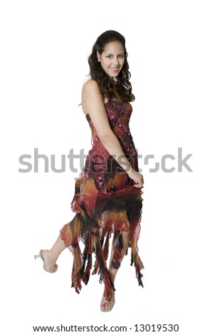 A teenage girl swirls around to show off her graduation/prom dress. - stock photo