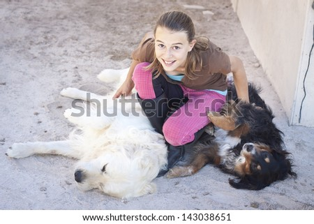 A teenage girl tickling two dogs