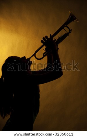 A teenage girl trumpet player isolated in silhouette against a yellow gold background.