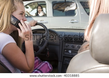 A teenage girl using her phone while driving and is going to be in a accident. - stock photo