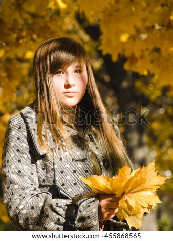 A teenage girl with a bouquet of autumn leaves - stock photo