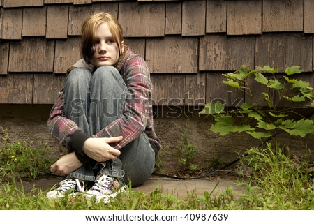 A teenage girl with a sad expression sits against a run-down house. - stock photo