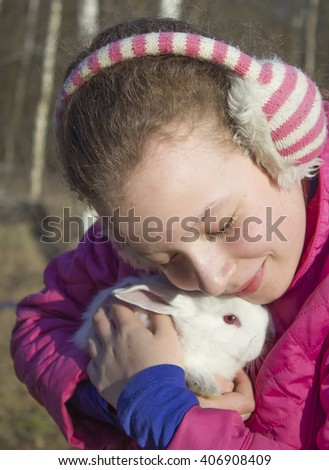 A teenage girl with a white fluffy rabbit