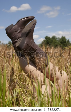 A teenage girls legs and cowboy boots sticking up over wheat in a wheat field outside on a beautiful summers day. - stock photo