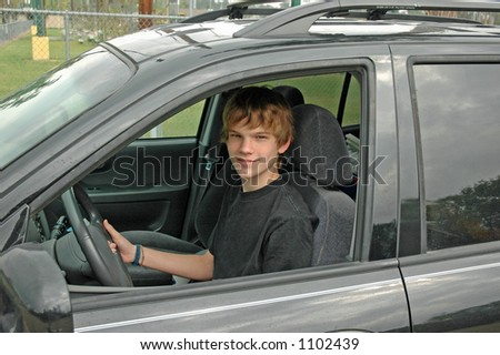 A teenaged boy drives his parent's sports utility vehicle - stock photo