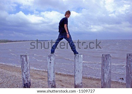 A teenaged boy stands balanced on posts at the shoreline of the ocean - stock photo
