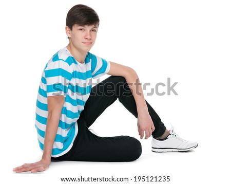 A teenager boy is sitting on the floor on the white background - stock photo