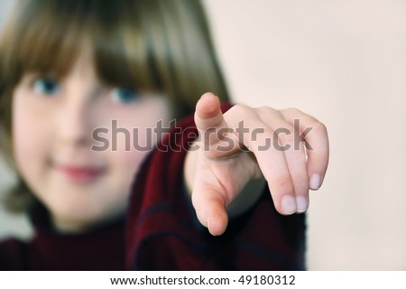a teenager girl pointing her finger forward - stock photo