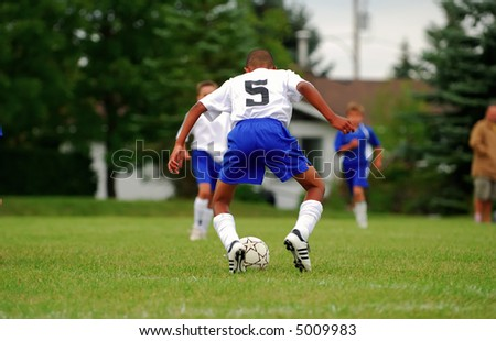 A teenager handles a soccer ball in a match.  Right hand and feet have very slight action blur.