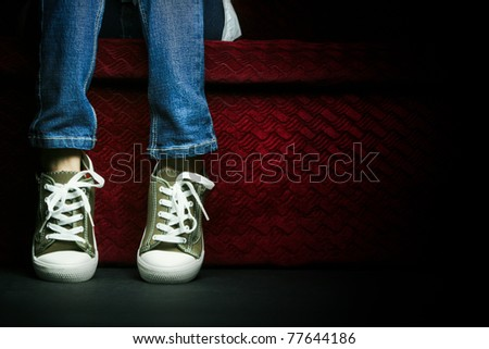 A Teenager showing her shoes and jeans, posing in studio. - stock photo