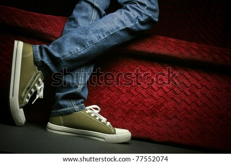 A teenager showing his/her shoes and jeans, posing in studio. - stock photo