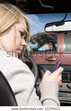 A teenager texting on her phone and looking away from the road where she is about to hit a truck with a woman in the drivers seat. - stock photo