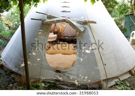 A teepee with an open flap to enter into it - stock photo