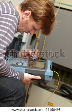 A telecom engineer working with reflectometer at site - stock photo