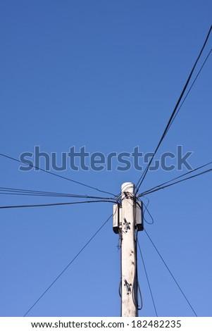 A telegraph pole against a blue sky - stock photo
