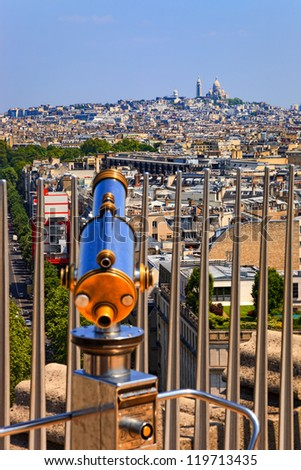 A telescope on the Arc de Triomphe in Paris with famous basilica of Sacre-Coeur in the background. - stock photo