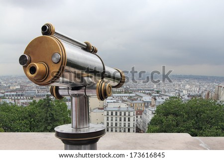 A telescope viewer overlooks view Paris skyline from the Montmartre, France - stock photo