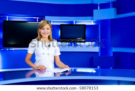 a television anchorwoman at studio during live broadcasting - stock photo