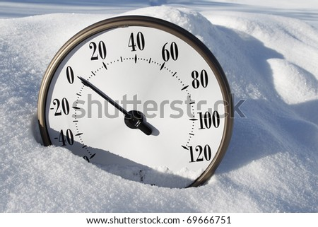 A temperature gauge in the snow reading around 0 fahrenheit. - stock photo