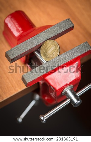 A ten rubles coin squeezed tightly in a metal bench vise as a concept of devaluation and financial crisis. - stock photo
