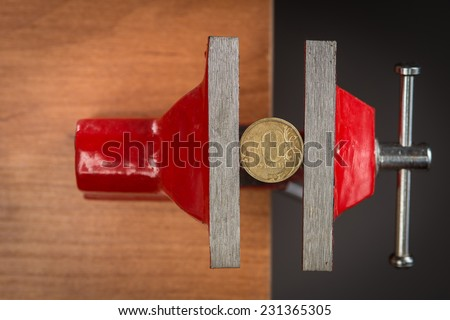 A ten rubles coin squeezed tightly in a vise tool, concept of devaluation and financial crisis. - stock photo