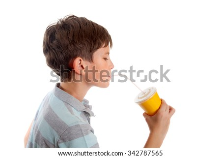 A ten years boy is drinking juice with plastic straw from yellow disposable cup