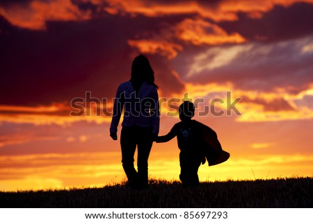A tender moment of a mom and her son walking along at sunset. - stock photo