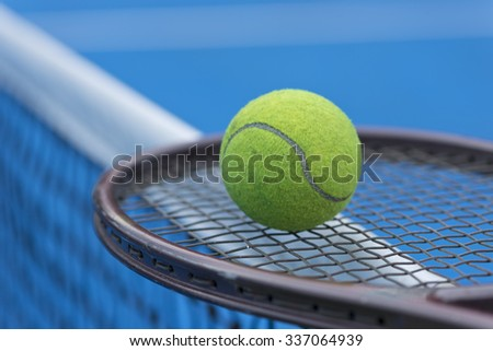 A Tennis ball and a racket at blue tennis court. - stock photo