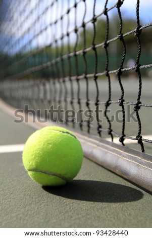 A tennis ball lies on the court next to the net - stock photo