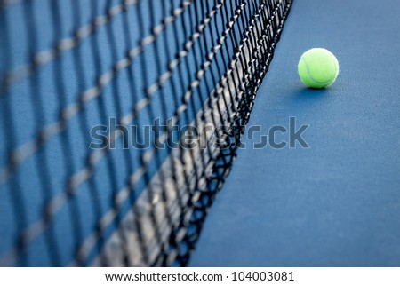 A tennis ball rests next to the net on a tennis court. - stock photo