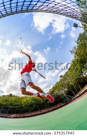 A tennis coach is practicing an smash next to the net while jumping. Enhanced version taken with fisheye. - stock photo
