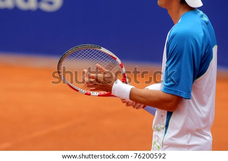 A tennis player prepares to serve a tennis ball during a match - stock photo