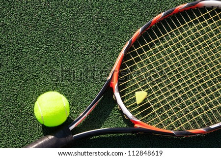 A tennis racket and new tennis ball on green court - stock photo