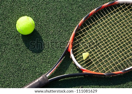 A tennis racket and new tennis ball on tennis court - stock photo