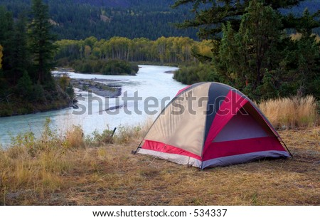 a tent by a river - stock photo