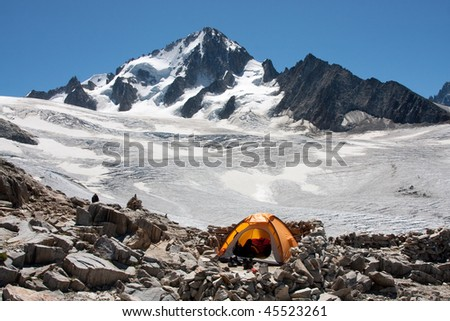 A tent is set up in a high mountain environment - stock photo