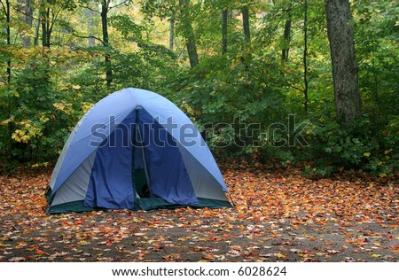 A tent sitting in a campsite in early autumn. - stock photo