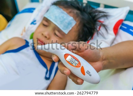 A termometer show a reading of fever on a little boy. Shallow dof, selective focus on the thermometer. - stock photo