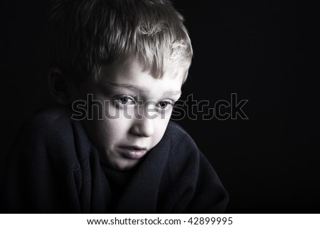 a terrified and fearful little boy flinches - stock photo