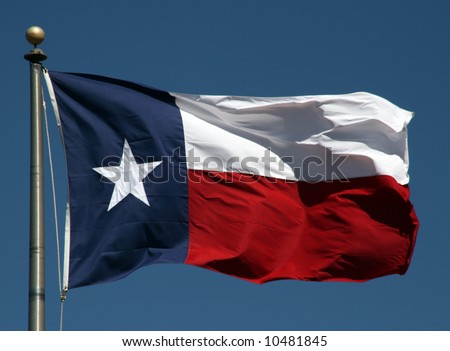 A Texas flag flapping boldly in the wind. - stock photo