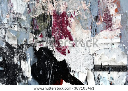 a texture closeup of torn posters with spray paint
