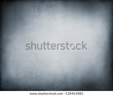 A textured paper background in cool black and white tones with a strong vignette effect and glowing center. - stock photo