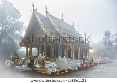 A Thai Buddhist temple sitting on a foggy mountain in Northern Thailand. The temple looks ornate and flanked by gold Buddha statues. A forest of misty trees surround the temple. - stock photo