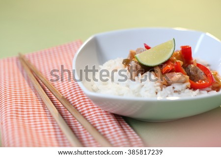 A thai dish of beef and paprika with rice and topped with lime. Accompanied with chopsticks. - stock photo