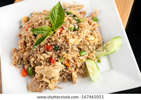 A Thai dish of chicken fried rice presented on a square white plate. - stock photo
